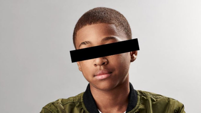 African American teenage boy with black bar over eyes