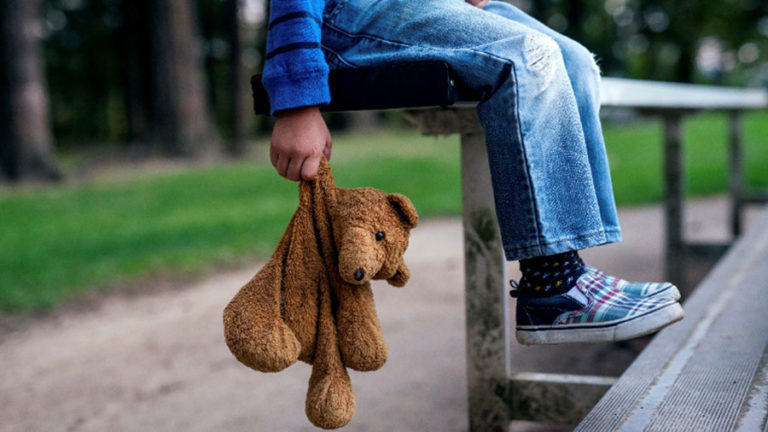 kid holding teddy bear on bench
