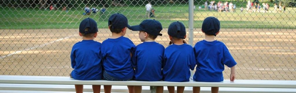 Kids sitting on a bench at a baseball field