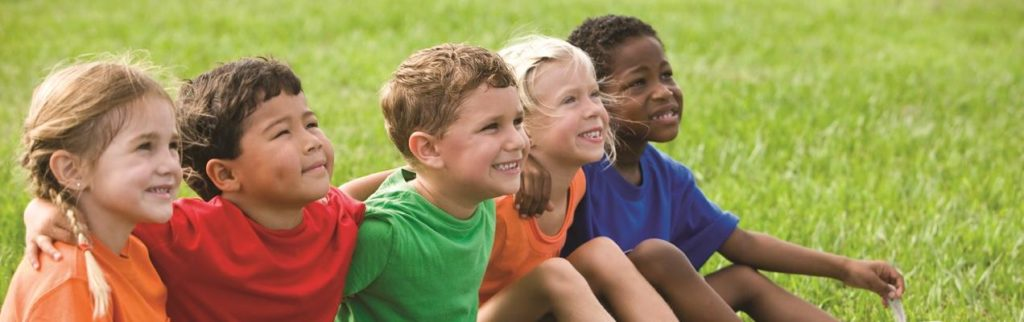 Children sitting on a field of grass