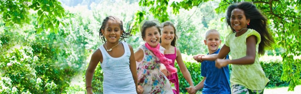 5 Children smiling outdoors.
